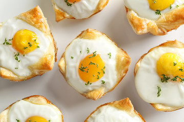 Tasty baked eggs in dough, closeup