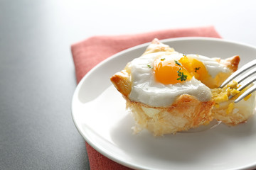 Tasty baked egg in dough with fork on plate