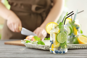 Mason jar of infused water with fruits and blurred woman on background