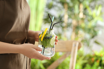 Young woman with jar of infused water outdoors