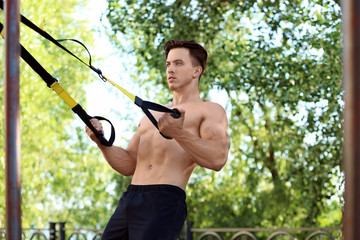 Handsome muscular young man exercising with TRX straps outdoors