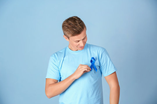 Young man wearing t-shirt with blue ribbon on color background. Prostate cancer awareness concept