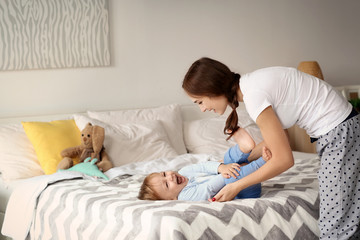 Beautiful young woman tickling her baby on bed at home