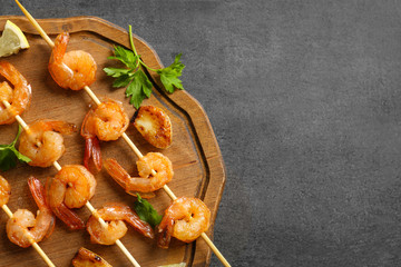 Delicious fried shrimps with garlic on wooden board, top view