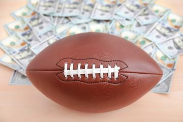 Football ball and money on table