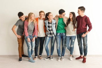 Group of cute teenagers near white wall