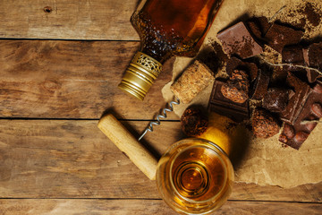 A glass of cognac or whiskey on a rustic table with chocolate and truffles.