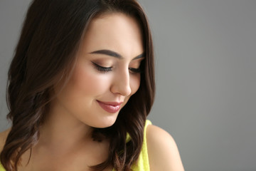 Young beautiful smiling woman on grey background, closeup
