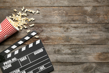 Movie clapper and popcorn on wooden background, top view