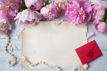 Pink peonies on a wooden background, red envelope and paper