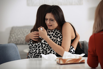 Young women comforting their friend indoors