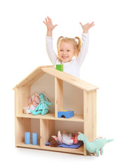 Cute little girl playing with wooden dollhouse on white background