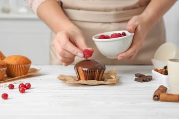 Female baker decorating tasty cupcake with raspberries at table