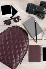 Composition with stylish backpack, camera and phone on wooden background