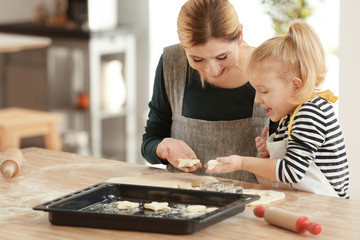 Mother and daughter with dough at table indoors