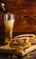 Hot dog with fried onions on a background of chips and beer on a wooden board