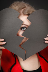 Young depressed woman covered by broken heart.