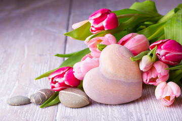Tulips, heart and stones on rustic light wooden background