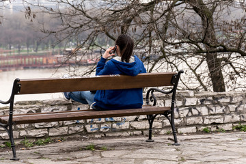 Belgrade, Serbia March 03, 2016: The girl sits on the bench, telephones and looks at the Sava River.