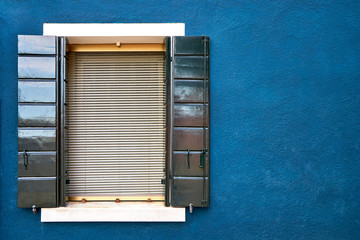 Window with green shutters on blue wall of houses. Italy, Venice, Burano.