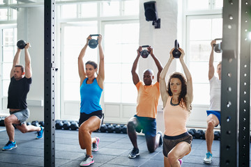 Focused people working out with weights together in a gym