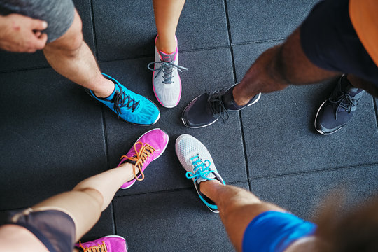 Diverse people wearing running shoes standing in a gym