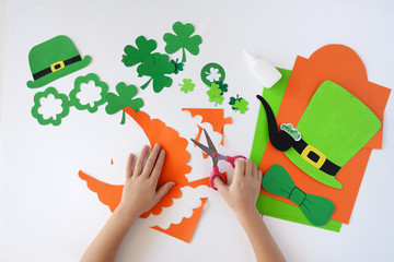 Top view.  Children's hands cut out a mask from paper for a St. Patrick's Day