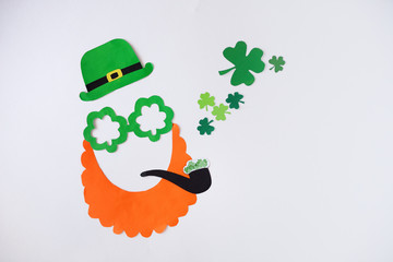 Mask of a handmade leprechaun from paper for a St. Patrick's Day on a white background