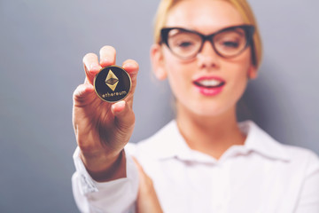 Woman holding a physical Ethereum coin cryptocurrency in her hand