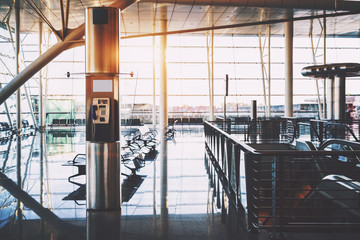 Payphone transparent cabin inside of contemporary airport terminal with empty screen mock-up above; interior of modern railway station with moving stairway, glass telephone booth, huge windows behind