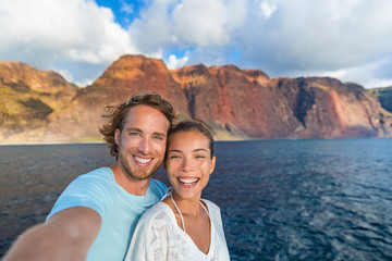 Wall Mural - Happy couple tourists on sunset cruise in Na Pali Coast Kauai, Hawaii taking selfie photo with mobile phone app. Smiling Asian woman and Caucasian man taking picture on summer holiday.