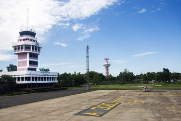 Air Traffic Control tower and Small plane stop on runway at Ubon Ratchathani International Airport in Thailand