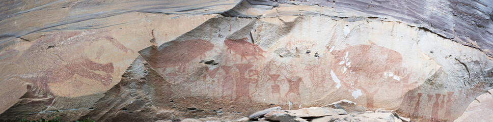 Rock art includes both humanoid and animal figures on cliffs at Pha Taem National Park in Ubon Ratchathani, Thailand