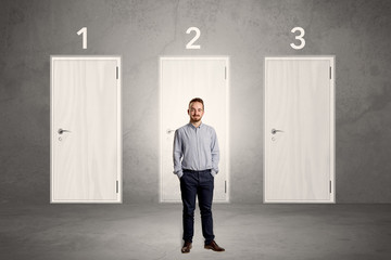 Businessman thinking in front of three doors