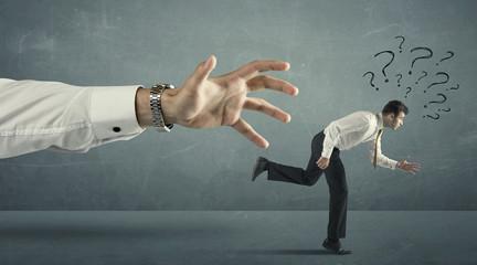 Businessman running away from a big hand