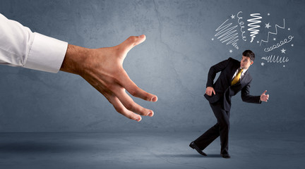 Stressful businessman running from a big hand