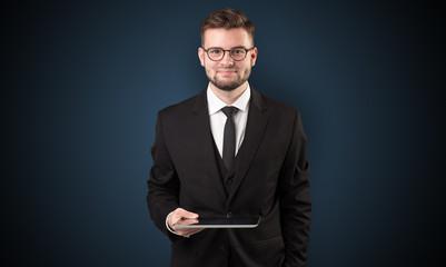 Businessman holding tablet with dark background