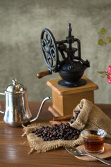 Vintage manual coffee grinder with coffee beans and cup