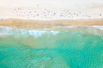 People swimming at the beach in summer with blue water from an aerial perspective