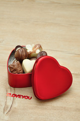 A heart shape tin filled with delicious small chocolates and the words I love you