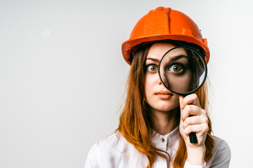 girl in an orange construction helmet gazing happily through a magnifying glass
