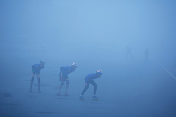 Boys skate on a road amidst heavy fog on a winter morning in New Delhi