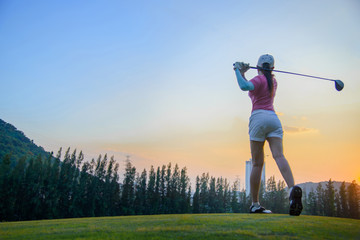 a woman golf player in an action at the ene of downswing, after hit the golf ball away from tee off to the fairway ahead by wood driver