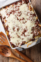 Million Dollar penne pasta with cheese and beef, close-up in a baking dish. vertical top view