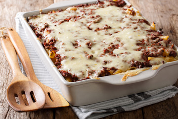 Million dollars pasta casserole with beef meat and cheese in a baking dish close-up. Horizontal