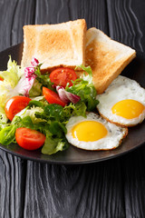 hearty breakfast: fried eggs with fresh vegetable salad and toast close-up. vertical