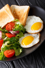healthy breakfast of fried eggs with fresh vegetable salad and toast close-up. vertical