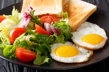 Organic breakfast of fried eggs with fresh salad and toast close-up. horizontal