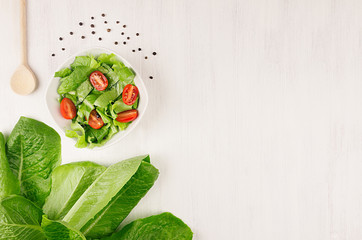 Healthy vegetarian salad of fresh tomatoes and spinach on white wood background, top view, copy space.