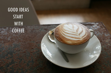 "Inspirational positive quote ""Good ideas start with coffee"" with leaf shape latte coffee on the rusty desk background."